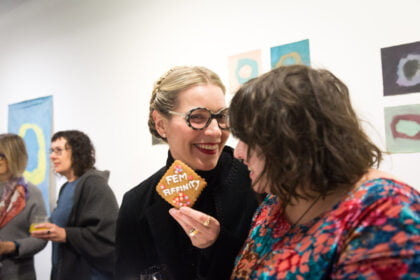 Curator Catherine Bell stands in the foreground alongside artist Eden Menta, who looks towards the cookie Catherine is holding in her hand which has the word 'FEM-AFFINITY' on it. Both are smiling at the opening of the 'FEM-AFFINITY' exhibition at Arts Project Australia in 2019, with artworks and people in the background.